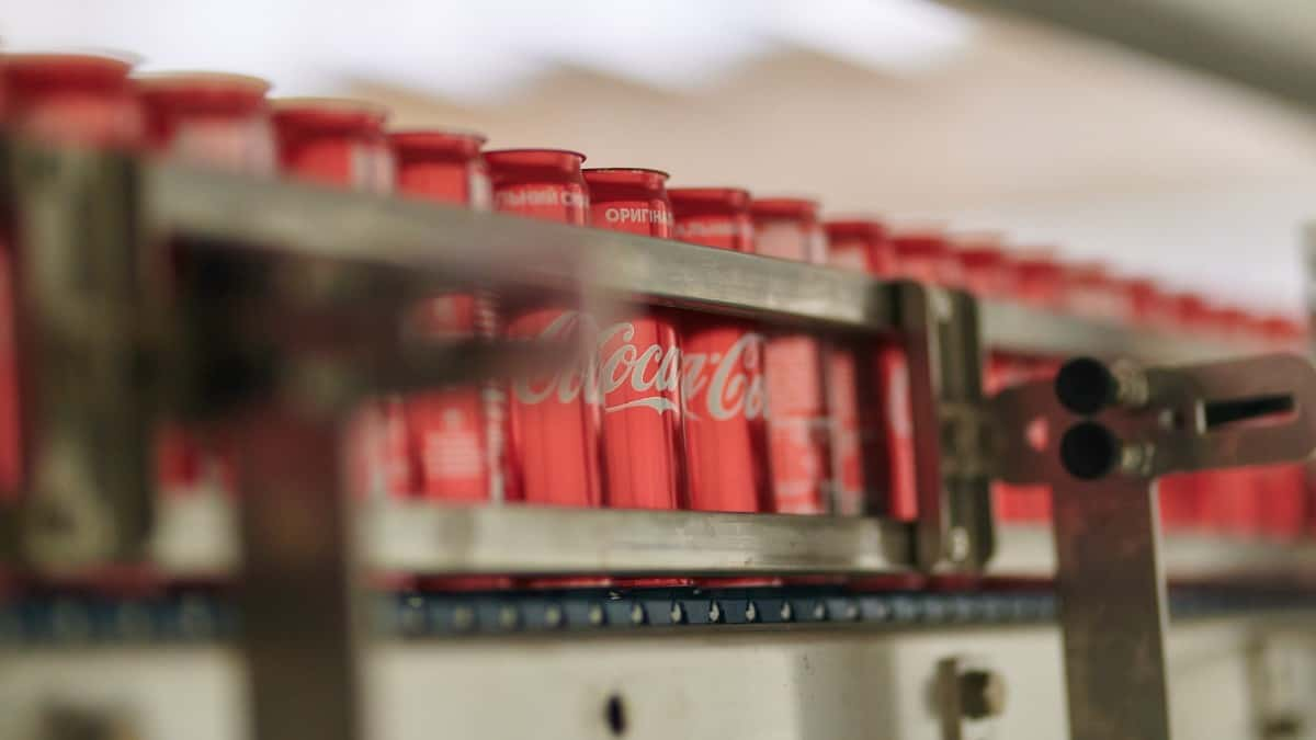 A line of Coca-Cola cans at a bottling plant