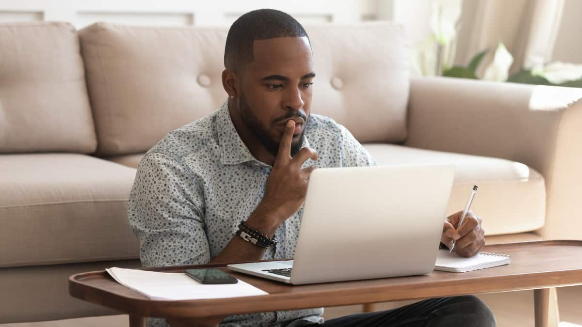 Concentrated young african american black guy sitting on heated floor at modern coffee table in living room, looking at laptop screen
