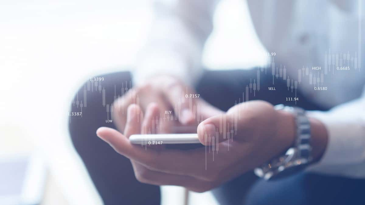 UK investor holding smartphone and monitoring shares