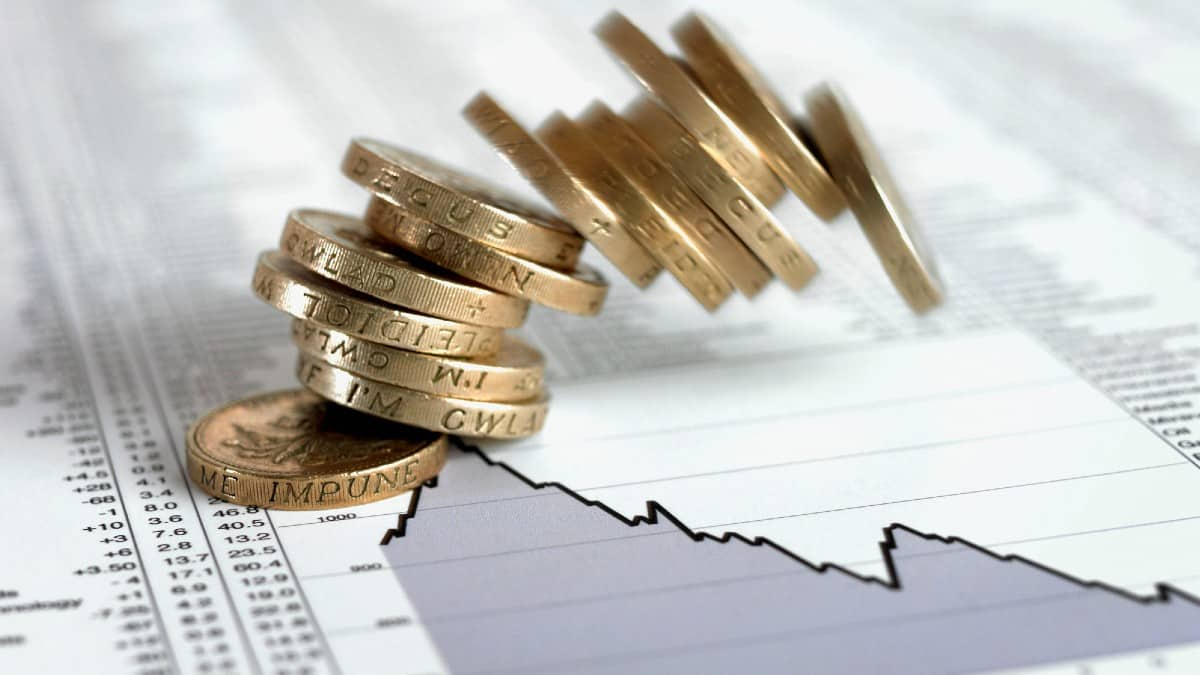 Stack of British pound coins falling on list of share prices