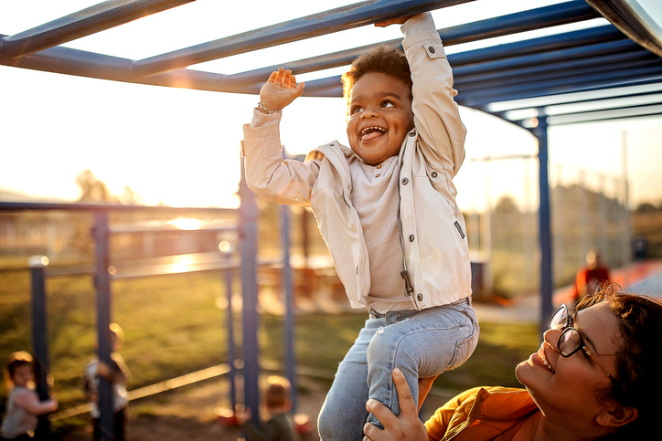 child on monkey bars showing the playfulness we can learn from kids