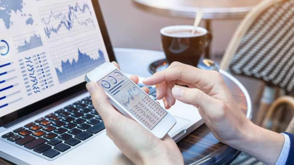Image of person checking their shares portfolio on mobile phone and computer