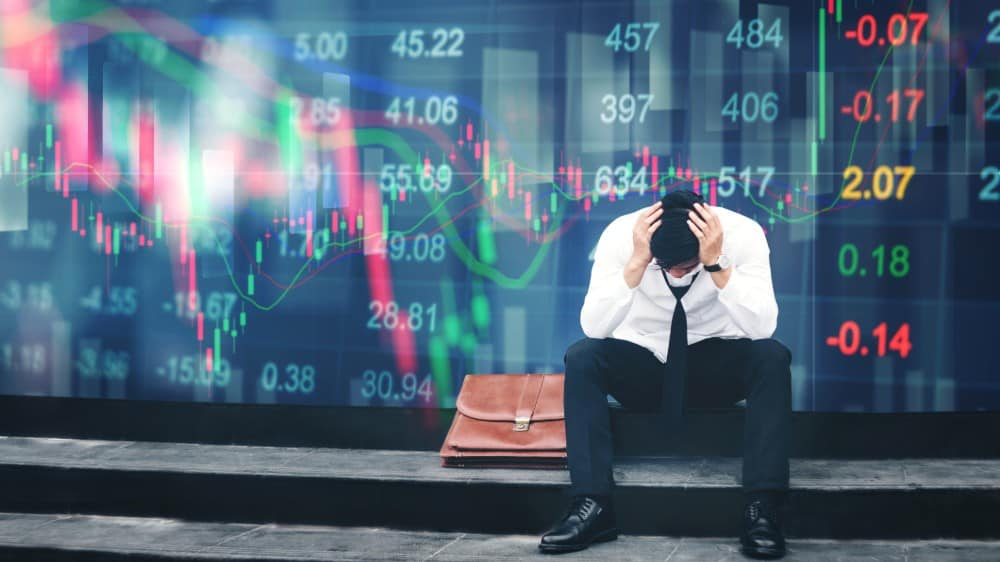 Tired or stressed businessman sitting on the walkway in panic digital stock market crash financial background
