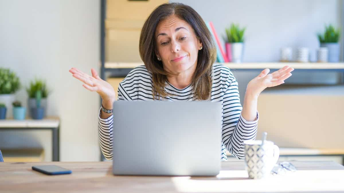 Middle age senior woman sitting at the table at home working using computer laptop clueless and confused expression with arms and hands raised.