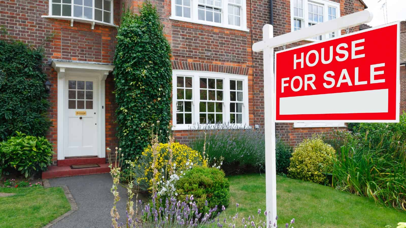 For sale sign outside a home in an affluent suburb of London