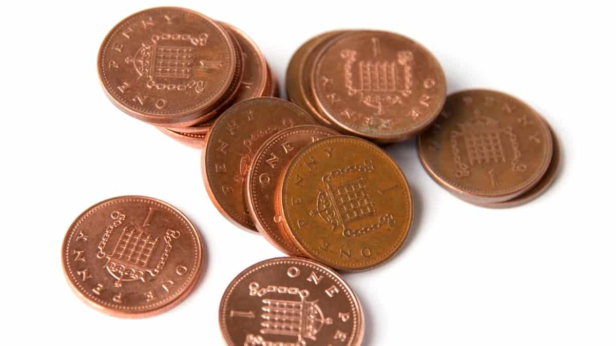 A pile of British one penny coins on a white background.