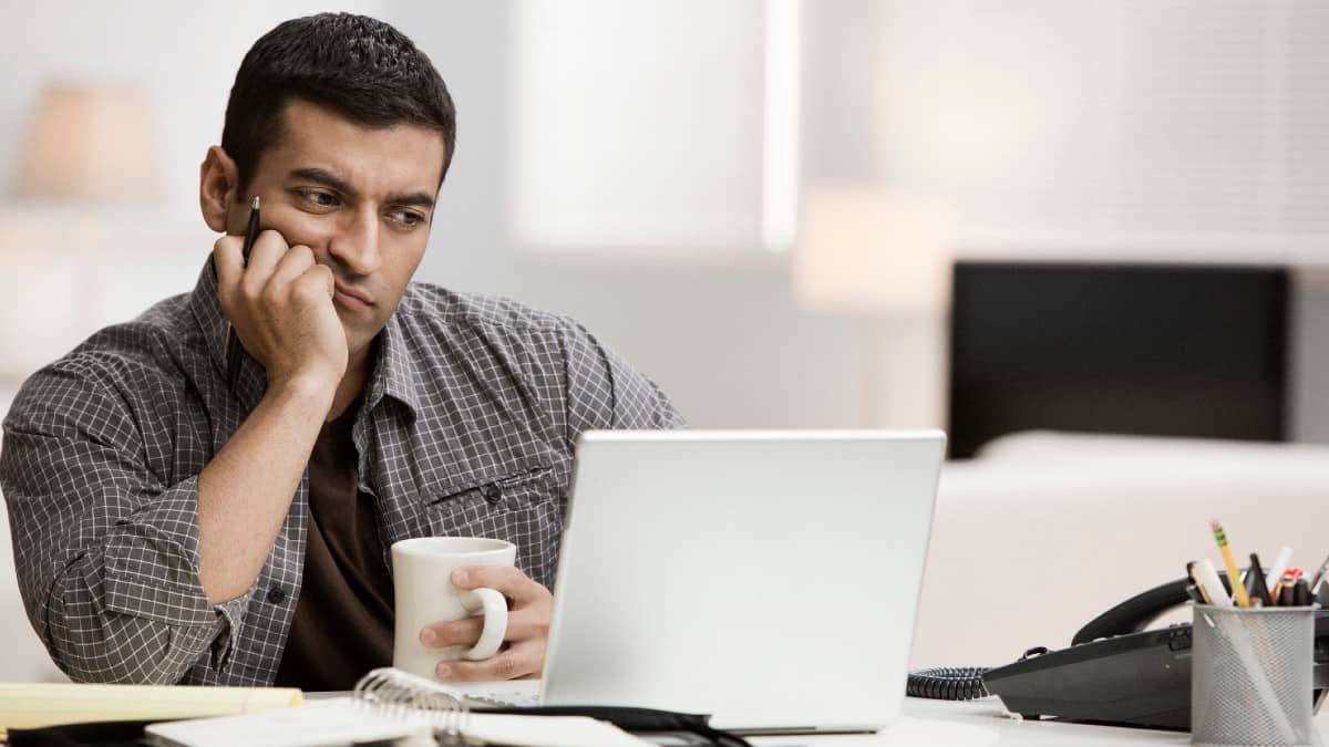 Hispanic man using laptop in home office and drinking coffee
