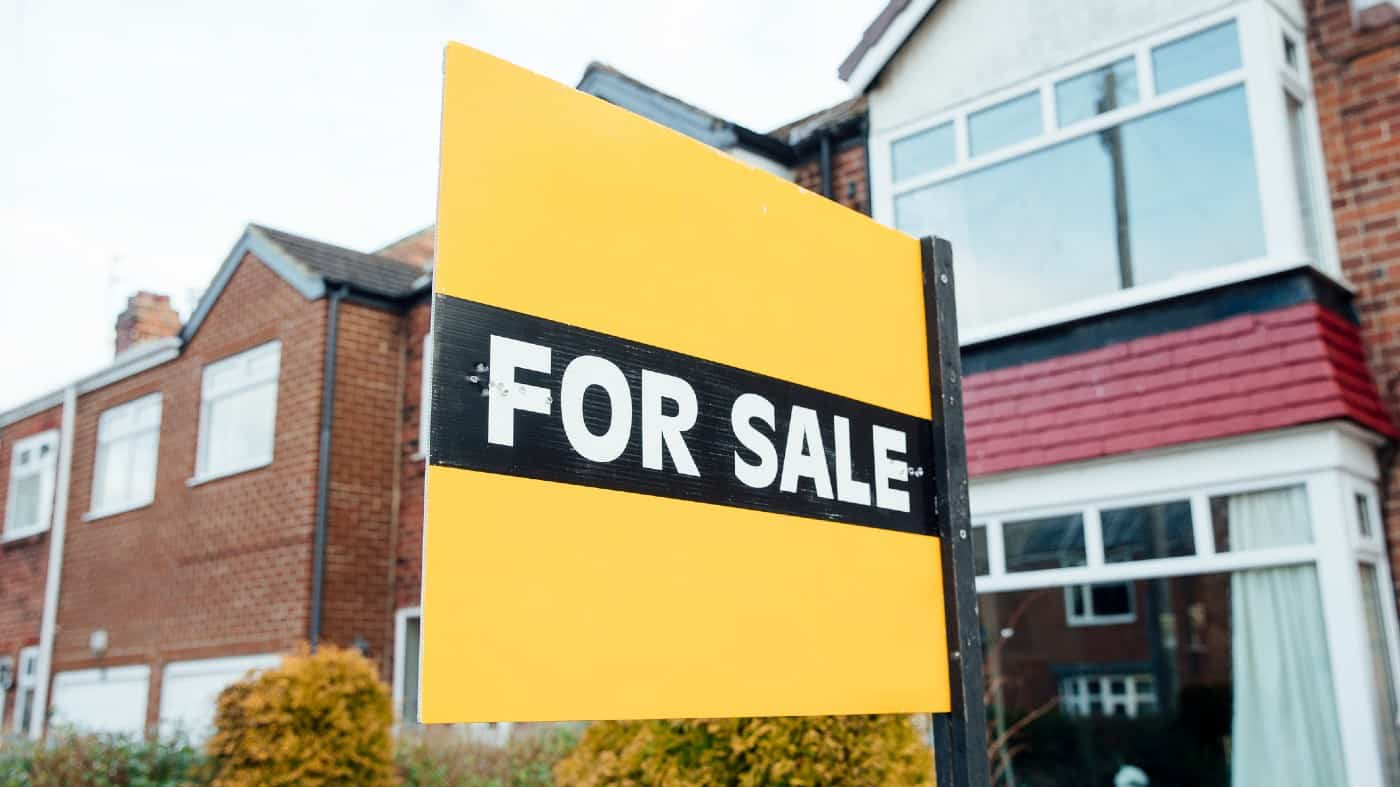 'For Sale' sign outside of a terraced house in the UK